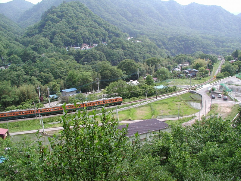 水没予定地の川原畑を走る吾妻線の普通列車。背後の山の中腹に川原湯温泉街。撮影の5日後にダムの補償基準が調印された。(2001年6月9日撮影)
