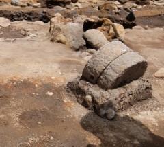 手前:使い込まれた石臼、後方:石を積んでつくられたカマド跡