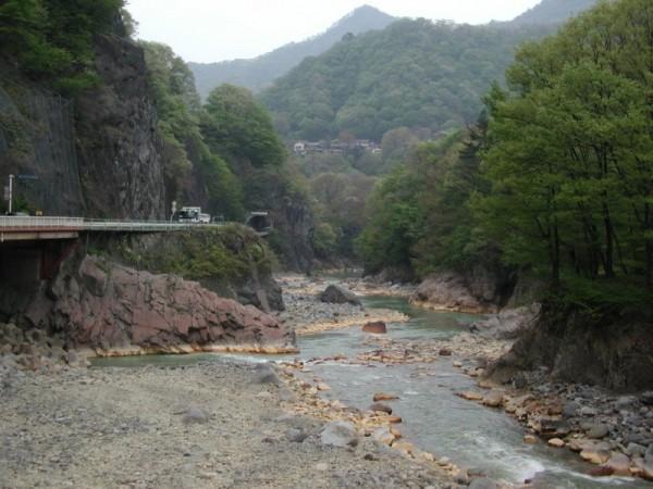 国道145号線沿いの川原湯岩脈・臥竜岩(がりゅうがん)。岩床の川原湯層の割れ目から、約230万年前、輝石安山岩の溶岩が流入してできた。柱状節理の岩が横たわって、龍が寝ている姿に似たところから名づけられた。山の中腹に川原湯温泉。2002年4月27日撮影