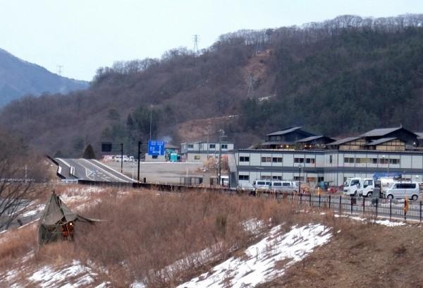本体工事を受注した清水建設JVの事務所が並ぶ川原湯の打越代替地。背後に旅館、手前で地すべり調査。(2015年1月26日撮影)