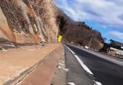 酸性熱水変質帯の影響で、付け替え国道の縁石やのり面は赤茶けて亀裂が入っている。2015年2月3日撮影
